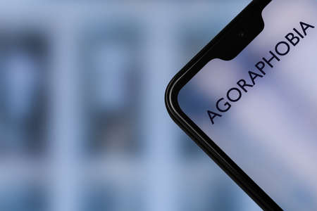 Photo pour Agoraphobia text on smartphone screen with blurred background of cold city, toned - image libre de droit