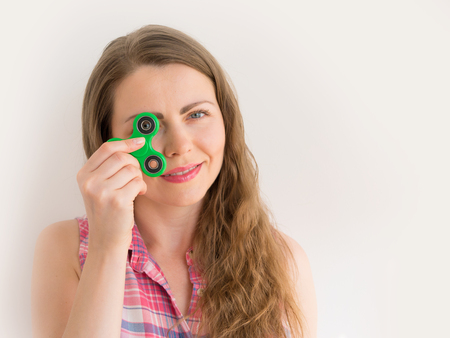 Girl playing with a colourful hand fidget spinner toy