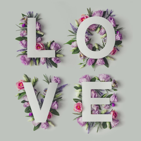 Foto de Creative layout with colorful flowers, leaves and Word LOVE. Love concept.Flat lay. - Imagen libre de derechos