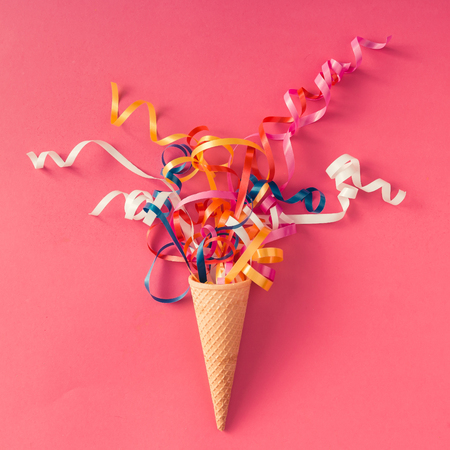 Photo pour Ice cream cone with colorful party streamers on pink background. Flat lay - image libre de droit