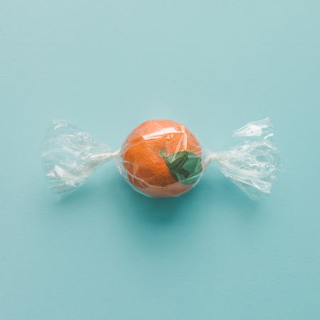 Orange wrapped like candy on bright blue background. minimal food concept.