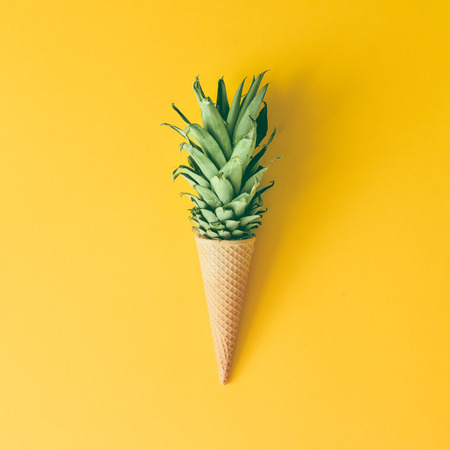 Photo for Ice cream cone with pineapple leaves on bright yellow background. Fruit and candy concept. Flat lay. - Royalty Free Image