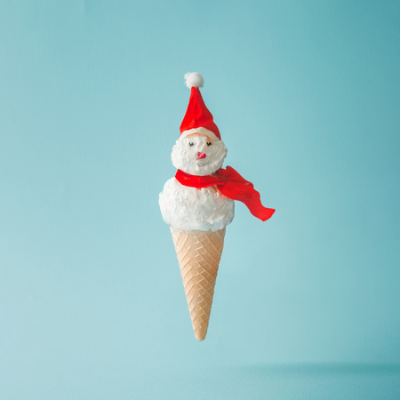 Foto de Snowman made of ice cream on bright blue background. Winter holiday concept. - Imagen libre de derechos