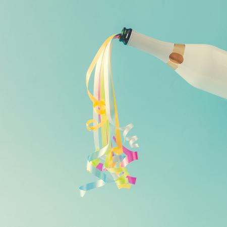 Foto de Champagne bottle with party streamers on bright blue background.  Party concept. - Imagen libre de derechos