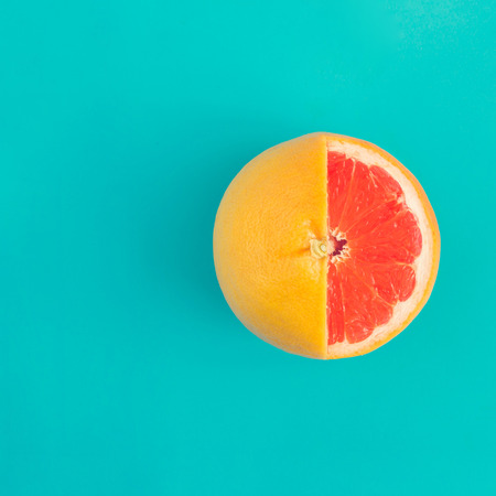 Foto de Red grapefruit on bright blue background. Minimal flat lay concept. - Imagen libre de derechos