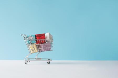 Foto de Shopping cart full with gift boxes. Minimal concept. - Imagen libre de derechos