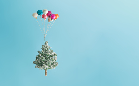 Photo pour Christmas tree lifted up by colorful balloon ornaments against sky blue background. New Year concept. - image libre de droit
