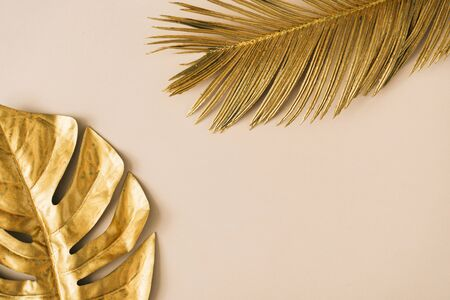 Photo for Creative layout made of golden tropical leaves and palms on beige background. Minimal summer exotic concept with copy space. Border arrangement background. - Royalty Free Image