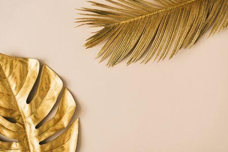 Foto de Creative layout made of golden tropical leaves and palms on beige background. Minimal summer exotic concept with copy space. Border arrangement background. - Imagen libre de derechos