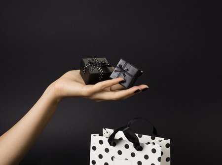 Photo pour Female hand holding a three black gift-boxes on a palm, black gift-bag decorated with white polka dots below. Black background. - image libre de droit