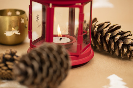 Christmas composition –red and golden lantern with lit candle, pinecone.