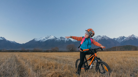 One caucasian children walk with bike in wheat field. Little girl walking black orange cycle on background of beautiful snowy mountains. Biker stand with backpack and helmet. Mountain bike hardtail.