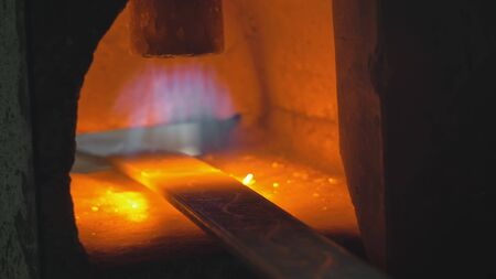 Photo pour Forge workshop. Smithy manual production. Gas furnace for heating metal. Modern melting stove for iron steel. The blacksmith makes iron products for manufacture of fireplaces, stoves. Cinematic look. - image libre de droit