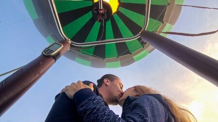 Adventure love couple on hot air balloon watermelon. Man and woman kiss hug love each other. Burner directing flame into envelope. Fly in morning blue sky. Happy people take selfie in hot air ballon.