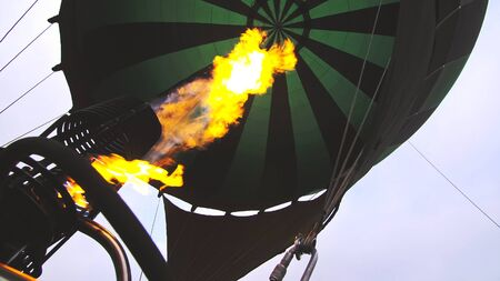 Photo pour Adventure on hot air balloon watermelon. Burner directing flame into envelope. The aircraft fly in morning blue sky due to hot air. Hot air burning gas fire to air balloon or aerostat during flight. - image libre de droit