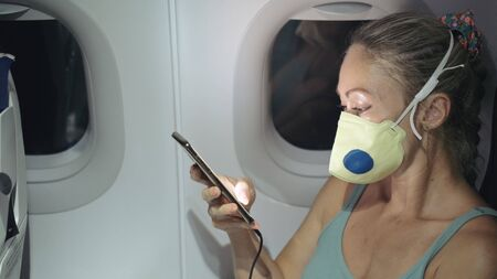 Foto de Woman travel tourist caucasian at plane aircraft with wearing protective medical mask. Read shock news about coronovirus at smartphone mobile. Virus coronavirus epidemic sars-cov-2 covid-19 2019-ncov. - Imagen libre de derechos
