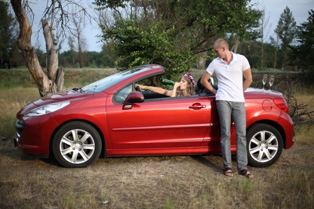 The girl in a red cabriolet drinks champagne, nearby there is a guy