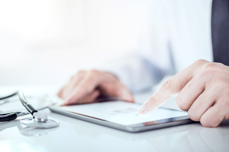 Photo pour Cropped image of a doctor working on his digital tablet.He is showing digital tablet with blank screen - image libre de droit