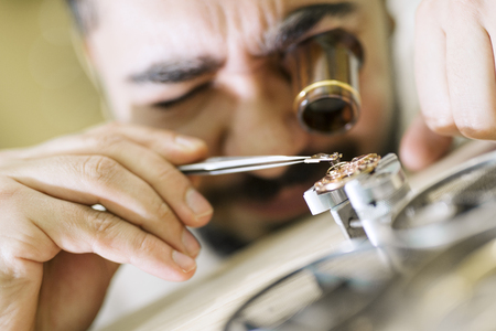 Close up portrait of a watchmaker at work. He is wearing specialist magnifying glass.Old pocket watch being repaired by watch maker