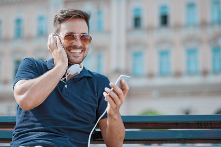 Close up of handsome young  man smiling while listening to music.