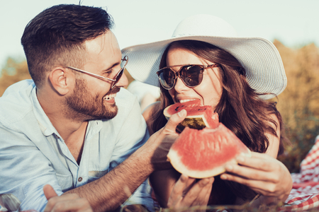 Photo for Young couple on a picnic together bite a one piece of watermelon. - Royalty Free Image