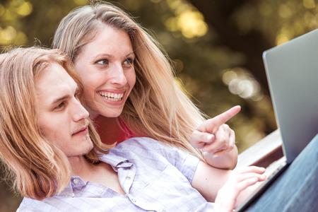 Foto de Beautiful happy couple with laptop sitting on bench and watching film outdoor. - Imagen libre de derechos