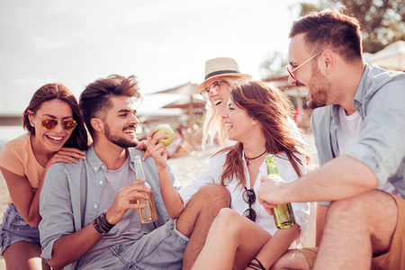Photo pour Group of cheerful young people relaxing on the beach. - image libre de droit