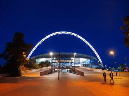 London, United Kingdom - May 22, 2009 : Brightly lit Wembley Stadium at night with people in front [description:]Wembley Stadium in London at night
