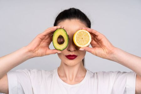 Photo pour Girl in white shirt holds the halves of the avocado and orange right next to the eye, the concept of beauty and health - image libre de droit