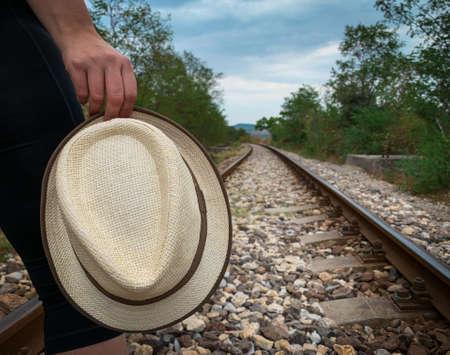 Photo pour A person holding a hat follows the railroad tracks way to the unknown - image libre de droit