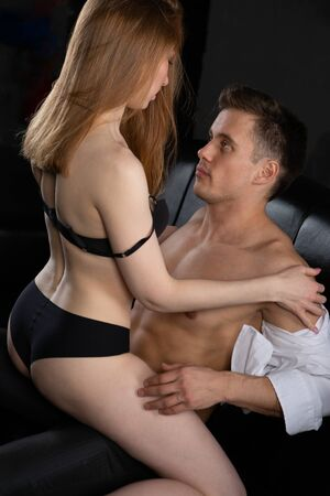 Photo pour a manly beefy handsome man embraces a sexy woman in black underwear sitting on top of him, they are sitting on a leather sofa in the bedroom - image libre de droit