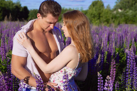 Photo pour An emotional sex scene, a young red-haired woman undressing her partner in a blooming bright field on a Sunny day - image libre de droit