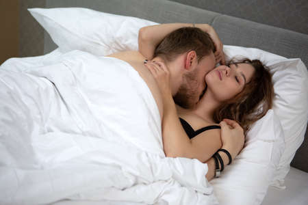 Photo pour young loving couple lying in each other's arms and kissing in bed at home - image libre de droit