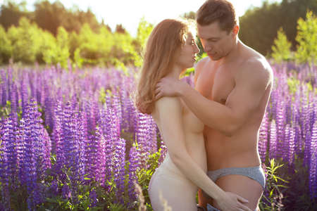Photo pour A young Nude couple lovingly embraces on a blooming field during a beautiful sunset - image libre de droit