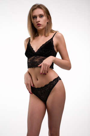 Photo pour A young blonde woman in Lacy black underwear with a gorgeous figure on a white isolated background. Close-up photo - image libre de droit