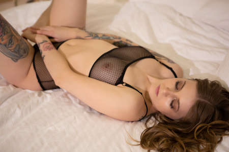 Photo pour Sensual portrait of a beautiful blonde girl with tattoos lying on the bed. - image libre de droit