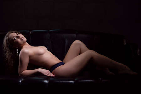 Photo pour a sexy Nude woman with a beautiful figure is lying gracefully on a black sofa - image libre de droit