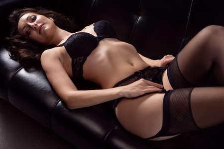 Photo pour Portrait of a young brunette woman posing in sexy lace underwear on a black leather sofa - image libre de droit