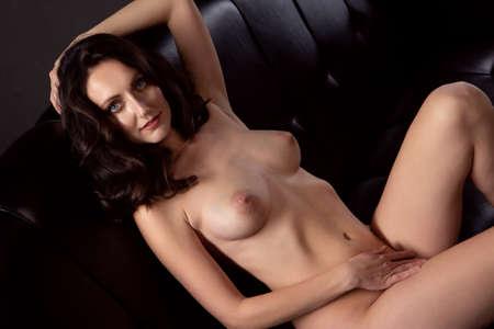 Photo pour Sexy nude brunette woman lying on a black sofa - image libre de droit