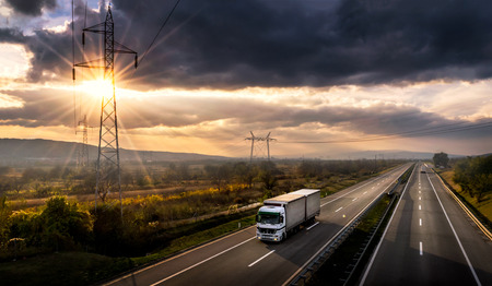 Photo pour Highway transportation with white lorry at sunset - image libre de droit