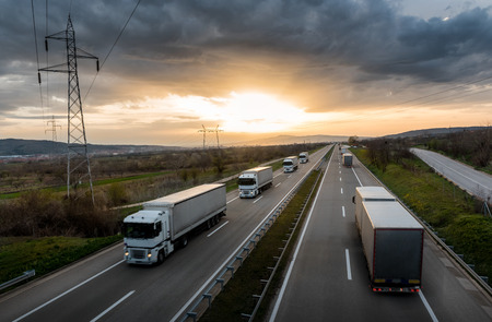Foto de Caravan or convoy of white trucks in line on a country highway at sunset - Imagen libre de derechos