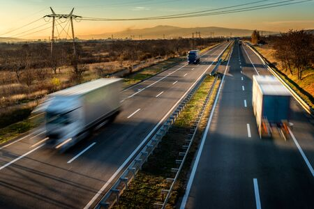 Delivery trucks in high speed driving on a highway through rural landscape. Fast blurred motion drive on the freeway. Freight scene on the motorway
