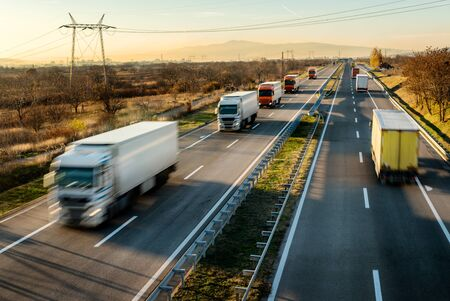 Photo for Convoy of Delivery trucks in high speed driving on a highway through rural landscape. Fast blurred motion drive on the freeway. Freight scene on the motorway - Royalty Free Image