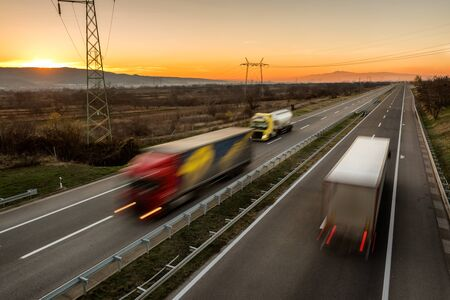 Photo for Delivery trucks and cars in high speed driving on a highway through rural landscape. Fast blurred motion drive on the freeway. Freight scene on the motorway - Royalty Free Image