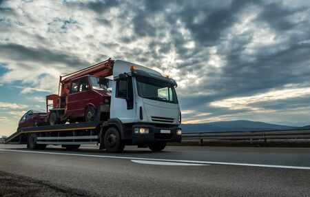 Photo for Tow truck or Flatbed truck towing two vehicles at dramatic sunset on a highway - Royalty Free Image