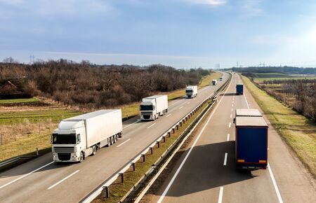 Foto de Highway transportation with a convoy of Lorry trucks passing trucks under a beautiful sunset sky - Imagen libre de derechos