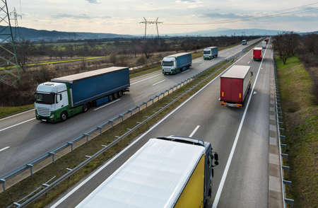 Photo for Convoys or caravans of transportation trucks passing on a highway on a bright blue day. Highway transit transportation with white and red lorry trucks - Royalty Free Image