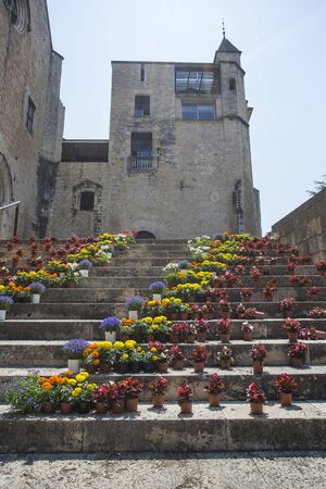 A staircase in a Gothic quarter decorated with flowers during the Tiempo de flores festival in Girona, Spain. Contemporary floristic art in ancient architecture