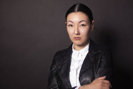 Photo for Serious asian woman looking directly at camera. Isolated on black background - Royalty Free Image