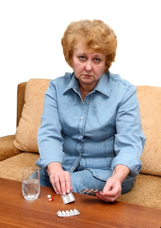 Senior lady woman with medication pills in room.